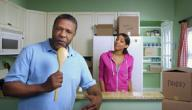 Dad Singing Into Wooden Spoon while Daughter Looks on Amused